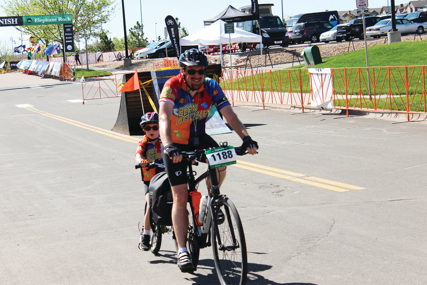 A man rides a tandem bike with his son as they both finish their ride June 2 during the Elephant Rock cycling event.