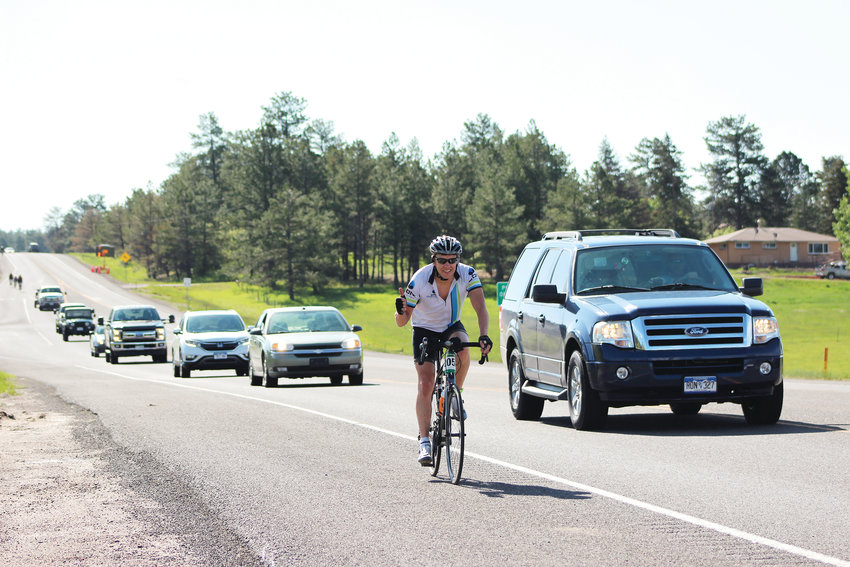 A cyclist smiles as traffic passes him on Highway 83 near Franktown June 2 during the annual Elephant Rock Ride.