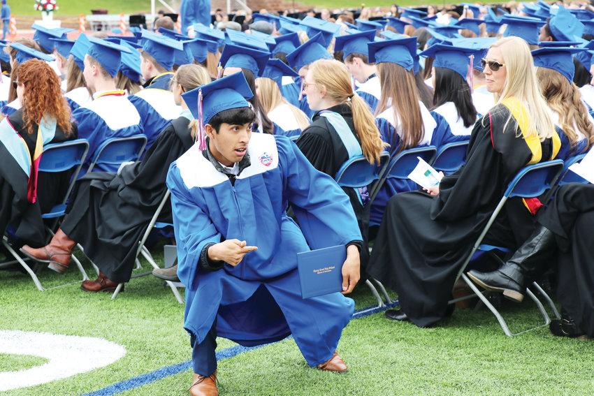 Student Luis Rogel strikes a pose after receiving his diploma at Cherry Creek High's graduation.
