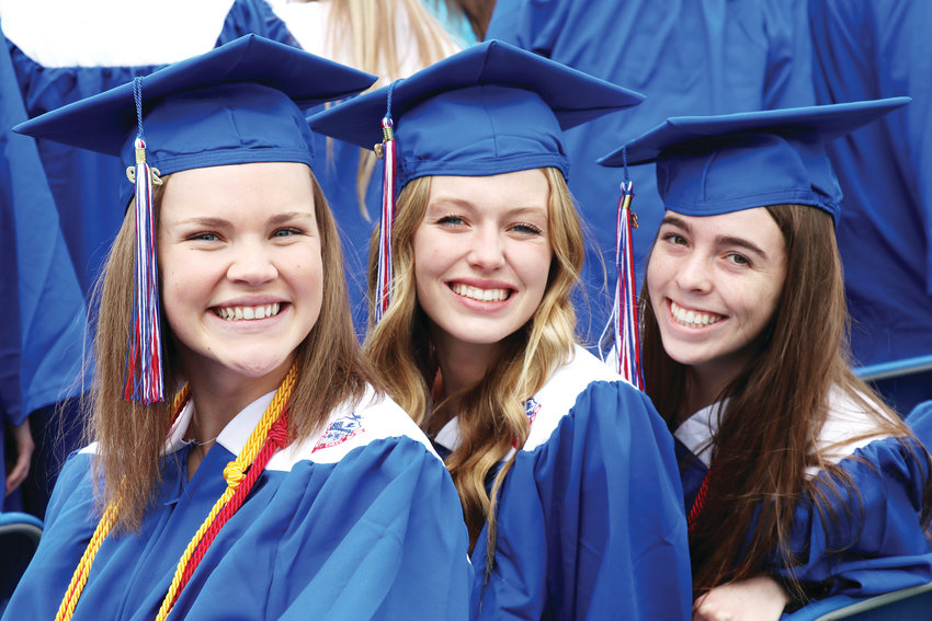 From left, students Katie Sherman, Brooke Schmidt and Sophie Shepard smile during the Cherry Creek High School commencement ceremony on the school's campus in Greenwood Village.