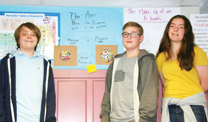 From left, Griffin Leapley, Matteo Bashford and Evangelene Jones stand by one of five group projects that entailed Drake Middle School's seventh-grade honors class' class project. The study about the A-bomb helped the students gain an understanding of how countries interact with each other while tying in science with their language arts studies of the Holocaust.