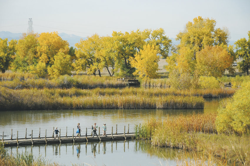People walk on the Lake Mary floating boardwalk at Rocky Mountain Arsenal National Wildlife Refuge in the Commerce City area.