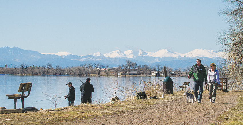 People walk with their dog as others fish at Barr Lake in the Brighton area.