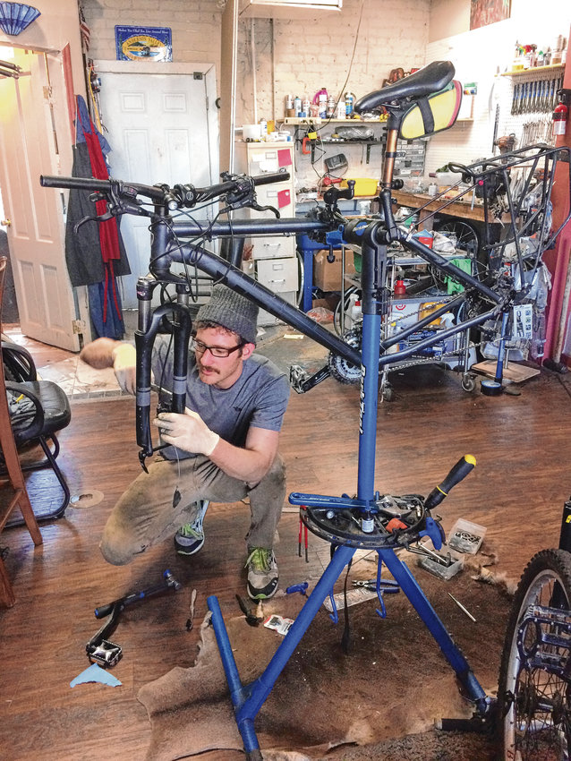 Dmitri Rumschlag works on a bike in his shop on Ogden Street in Capitol Hill. In addition to walk-in repairs, customers can become members at Z Cycle Shop, which gives them access to more products at the store.