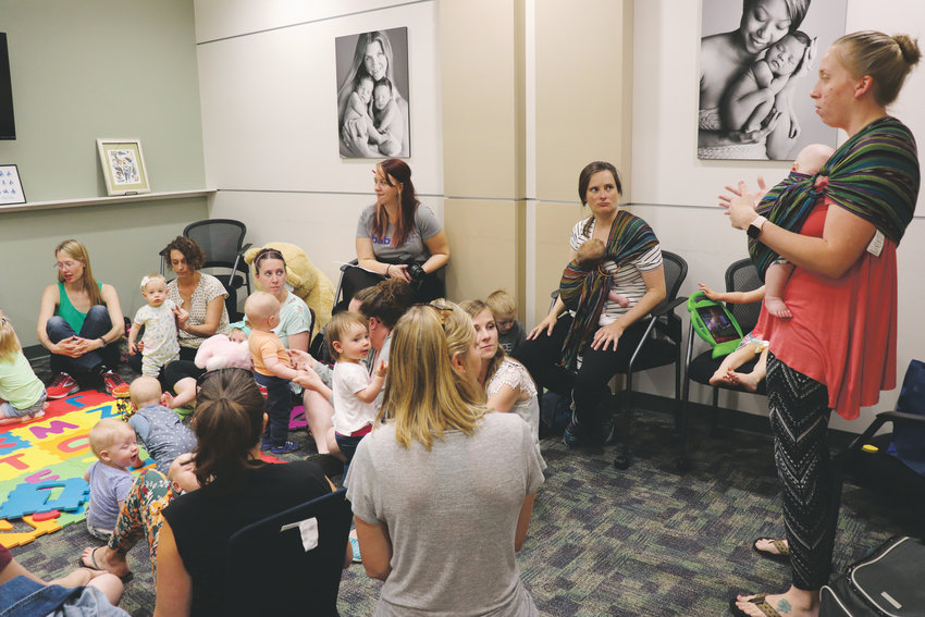 Certified consultants show moms at the Baby Cafe how to use ring slings to carry their babies.
