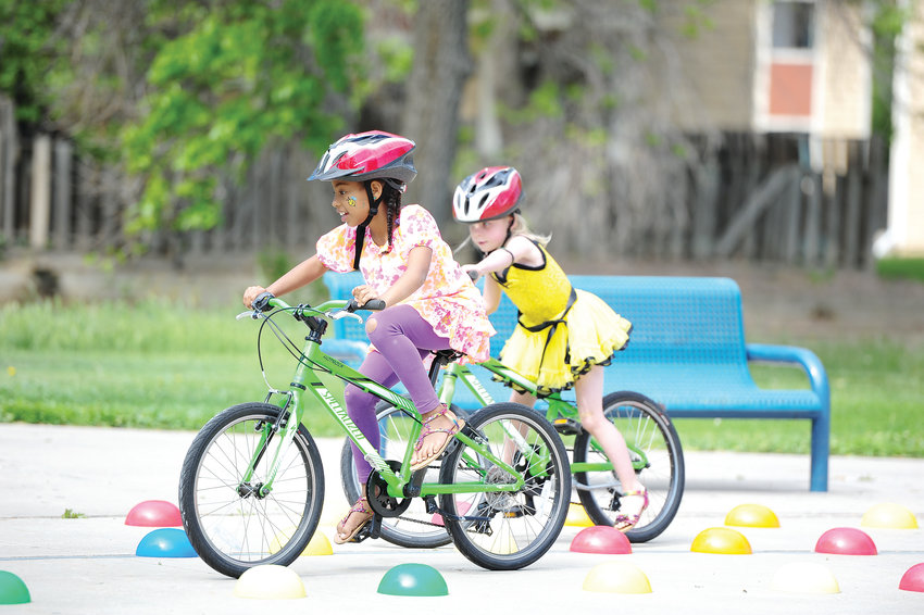 Anikka Bevjak, 9, left, and sister, Dreya, 5, of Thornton, negotiate a bicycle course, set up by Bicycle Colorado, during Northglenn's Annual Derby Day June 1 at E. B. Rains, Jr. Park.