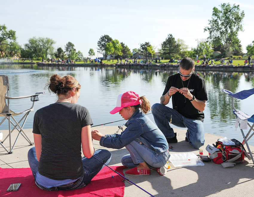 Corey Peterson, right, of Broomfield, readies a fishing line for his daughter Taryn, as wife Danielle looks on, just prior to the official start of Northglenn's Annual Fishing Derby, held June 1 at E.B. Rains, Jr. Park.