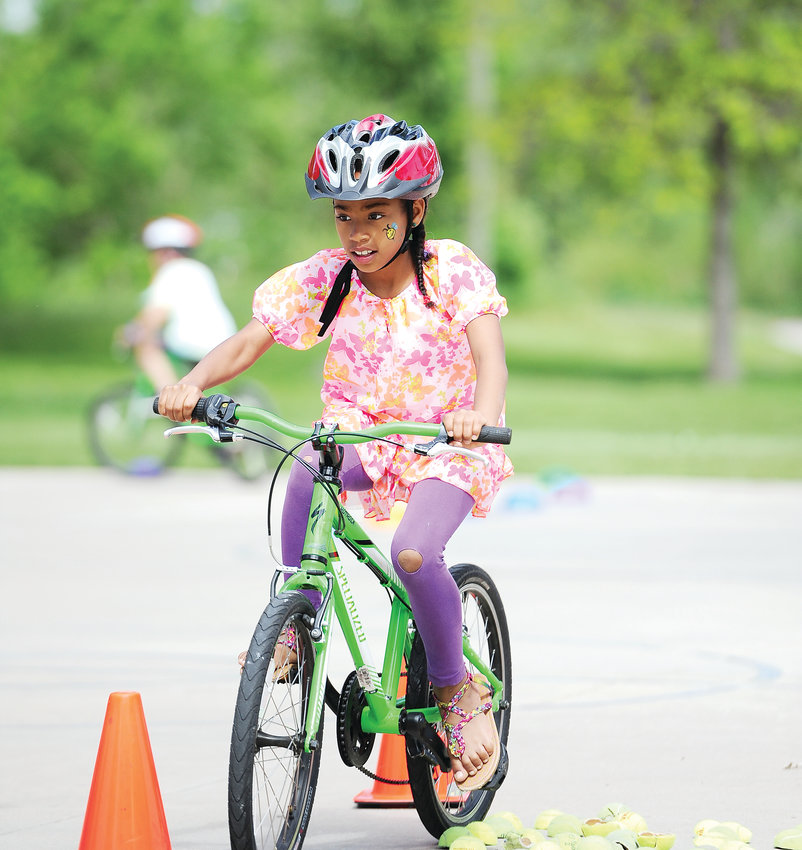 Nine-year-old Anikka Bevjak, of Thornton, negotiates a Bicycle Colorado obstacle course, which had been laid out on the basketball court of E.B. Rains, Jr. Memorial Park, as part of Northglenn's June 1 Derby Day.
