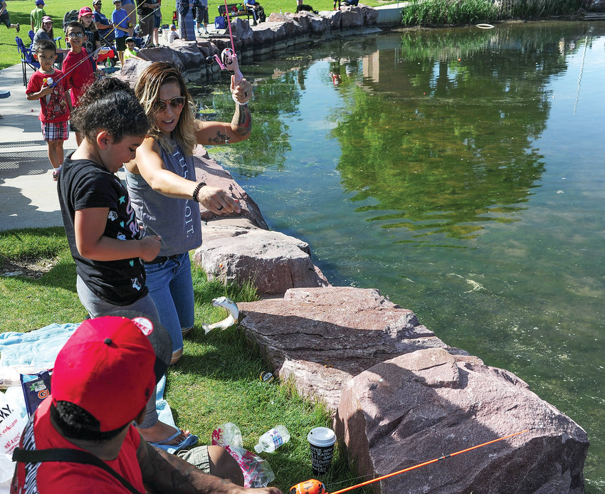 Monica Avila, right, of Northglenn, helps her daughter Raiin, 6, land a rainbow trout, as her father Dennis looks on, during Northglenn's Annual Fishing Derby June 1 at E. B. Rains, Jr. Park. Nearly 250 area youngsters signed up for the event, according to Northglenn officials.