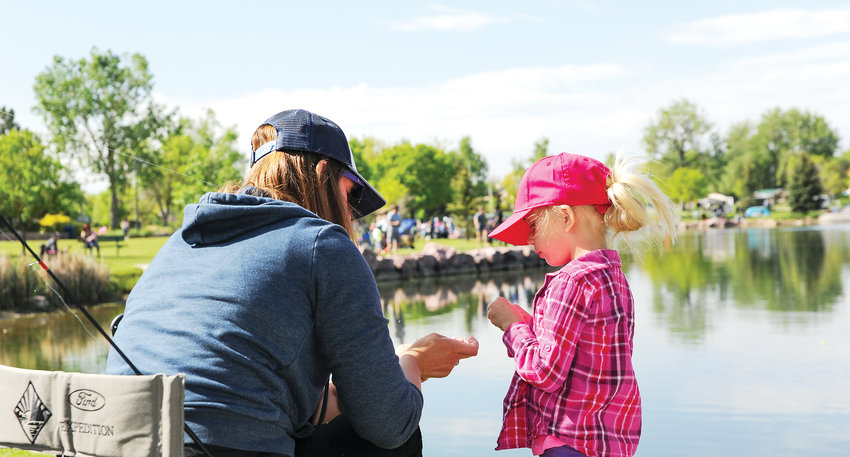 Adelyn Forristall, 5, of Northglenn, gets help with her fishing line from her mother Justine, during Northglenn's annual Fishing Derby June 1, at E. B. Rains, Jr. Park.