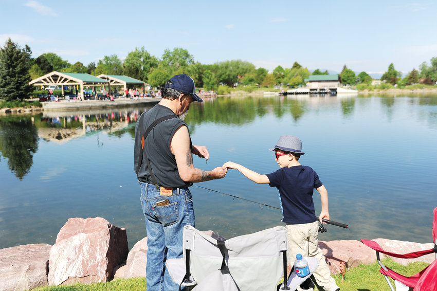 "Emilio Cos y Leon, left, of Thornton, helps grandson Caleb, of Frederick, tie a line on, during Northglenn's Annual Fishing Derby June 1 at E. B. Rains, Jr. Park. Having had no luck, the elder Cos y Leon later said, ""that's why it's called fishing and not catching."""