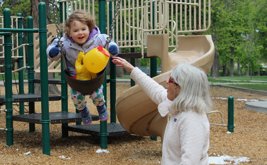 Meg Harlow, left, pushes her granddaughter, Vivian Paterson, on the swings at Cheesman Park.