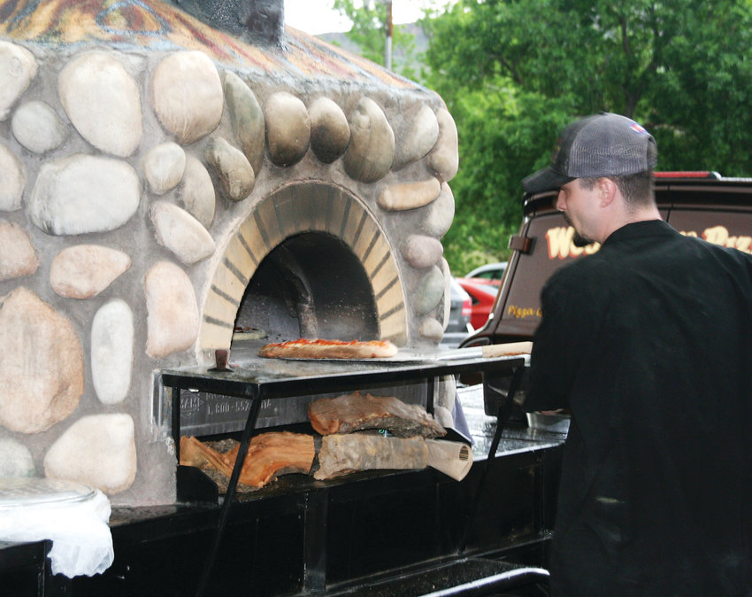 Bubba Torr, assistant kitchen manager at Woody's Wood Fired Pizza pulls a pepperoni pizza out of the restaurant's mobile oven on June 5 outside of the Golden History Museum during an event to celebrate an exhibit opening that recognizes Golden City Brewery and Woody's Wood Fired Pizza's 25th anniversary.