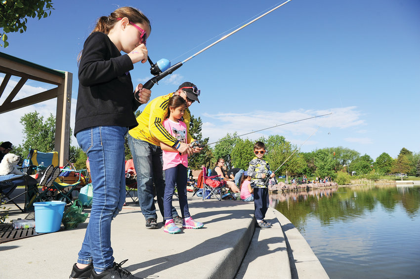 Antonio Soto, of Westminster, center, assists daughter Sadia, 7, with her fishing rod, as siblings Theresa, left and Victor, look on, during Northglenn's Annual Fishing Derby June 1, at E. B. Rains, Jr. Park.