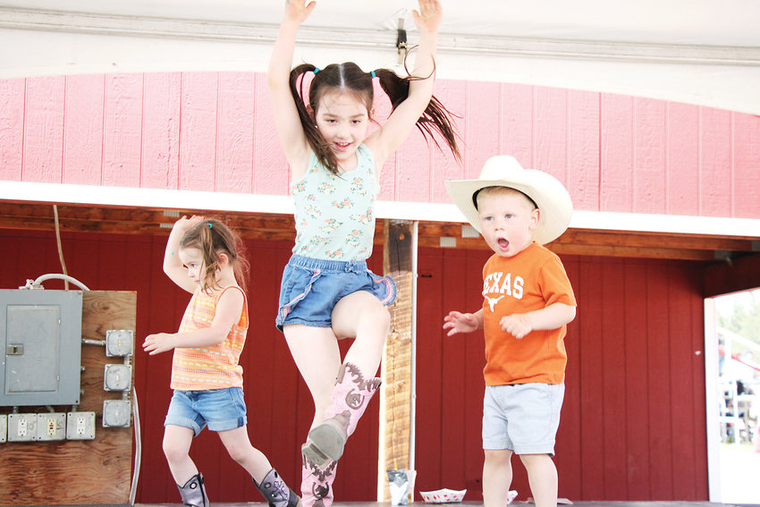Three-year-old Madison Divis, left, her sister Charlie Divis, 5, and Bo Rotondo, 2, burn off a sugar rush on one of the Stampede's stages.
