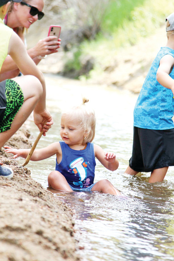 Kaitlee Dwitley sits in the creek while her mother, Heather, takes a photo and siblings play nearby during the annual Ducky Derby in Castle Rock.