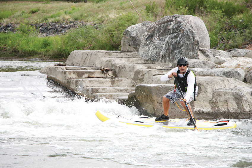 "J.B. Breidenbaugh, owner of Altitude Paddleboards in Littleton, catches a wave below a new ""hydraulic wave shaper"" along the South Platte River. The wave is one of an increasing number of aquatic amenities along the formerly-neglected waterway."
