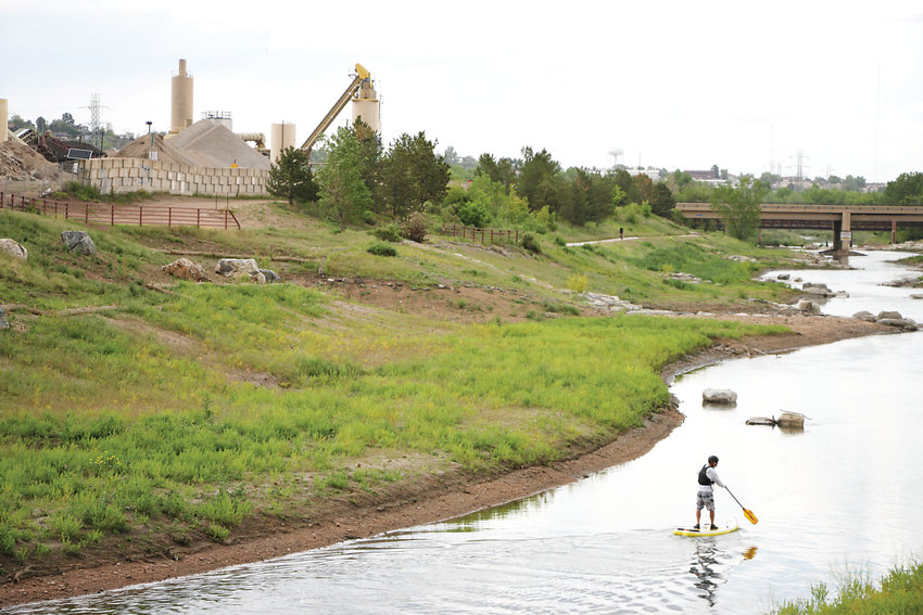 J.B. Breidenbaugh, owner of Altitude Paddleboards in Littleton, glides down the South Platte River along a newly-dedicated stretch of the Mary Carter Greenway Trail.
