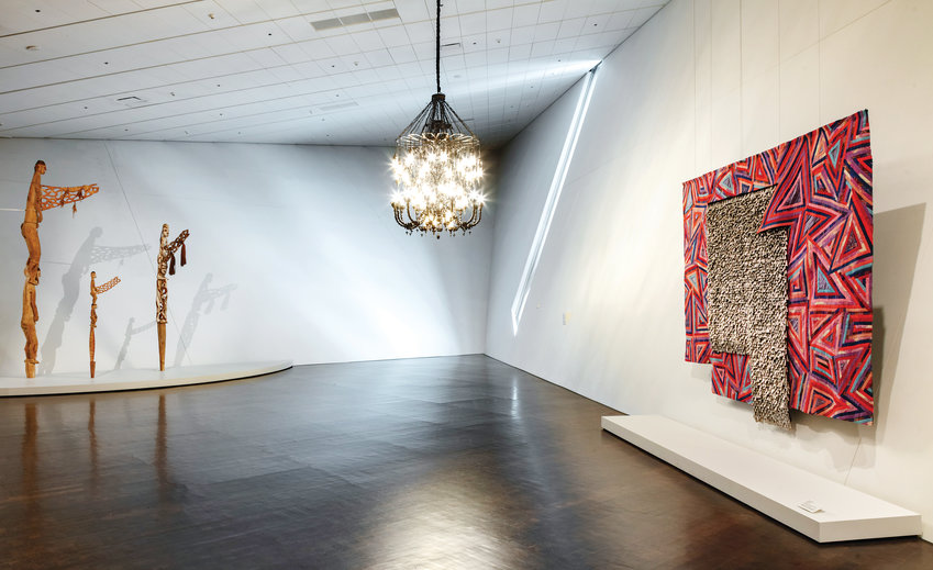 """The Way the Moon's Afraid of the Dark,"" a sculpture/chandelier by Fred Wilson, hangs near ""Rain Has No Father"" by African artist El Anatsui in the ""Light Show"" at Denver Art Museum."
