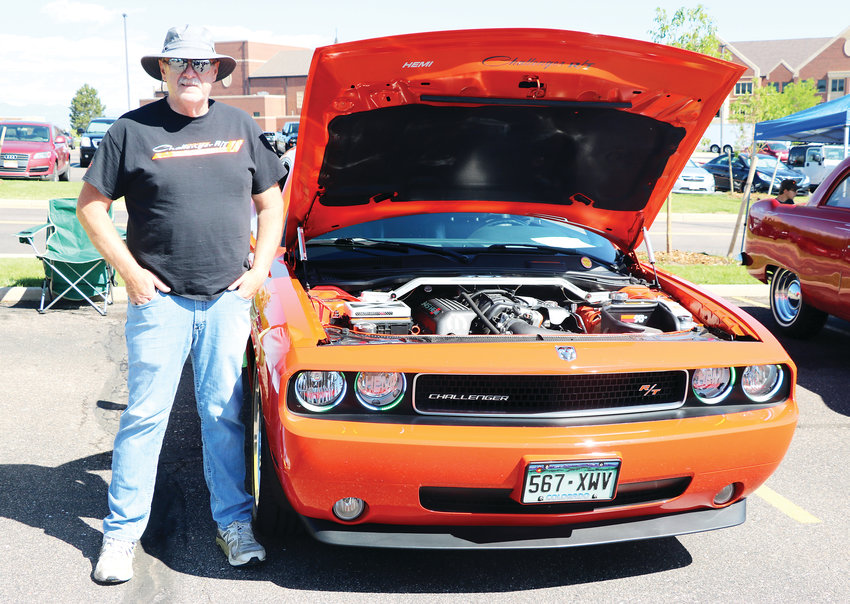 "John Wanniger stands beside his 2010 Dodge Challenger at HRCA's Classic Car Show on June 8 in the parking lot at Cherry Hills Community Church. ""When I was a kid,"" the car enthusiast said, ""I used to have cars and fix them up."""