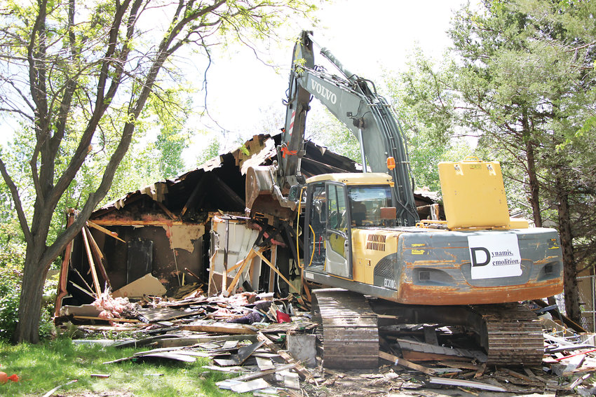 An excavator tears into a home on South Windermere Circle on May 31. The home, owned by David Lynch, caught fire in March the day before a hearing to determine whether it should be torn down after years of violations.