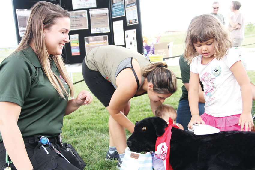 Three-year-old Amelia Olmeda scans Milo the stuffed dog's microchip, a small piece of technology that can be implanted in pets to help locate them. Helping her is Ashton Dailey, an animal control officer with the Arapahoe County Public Works and Development Department, which held its annual Play Date event June 7.