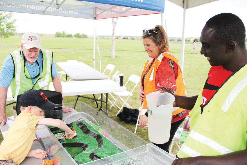 Joseph Boateng, right, an engineer with the county public works department, watches with other staff as a child tinkers with a model that lets visitors plan an imaginary development that involves flooding at the department's annual Play Date event.