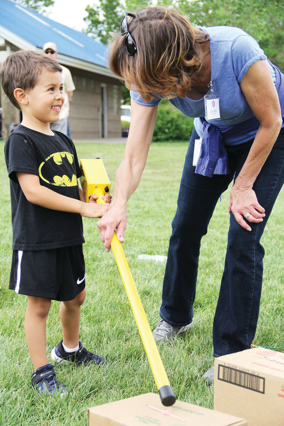 Andrew Largaespada, 4, tests types of metals with a metal detector with the help of Judy Ligrani, a support services staff member at the county public works department. Kids matched metals that they could see with metals hidden under boxes.
