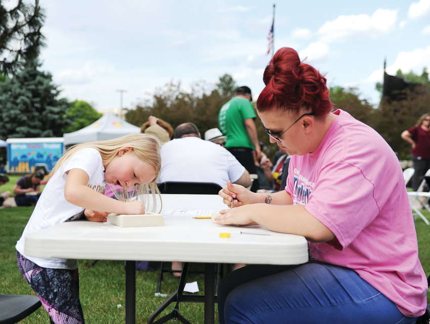 Kaydence Stiebs, 7, left, and her mother Samantha, of Northglenn, work on their sculpted block designs, during Northglenn's Community Iron Pour June 5, outside of City Hall. Residents were invited to submit their own creations, which were then filled with molten iron by a group of metal artists.