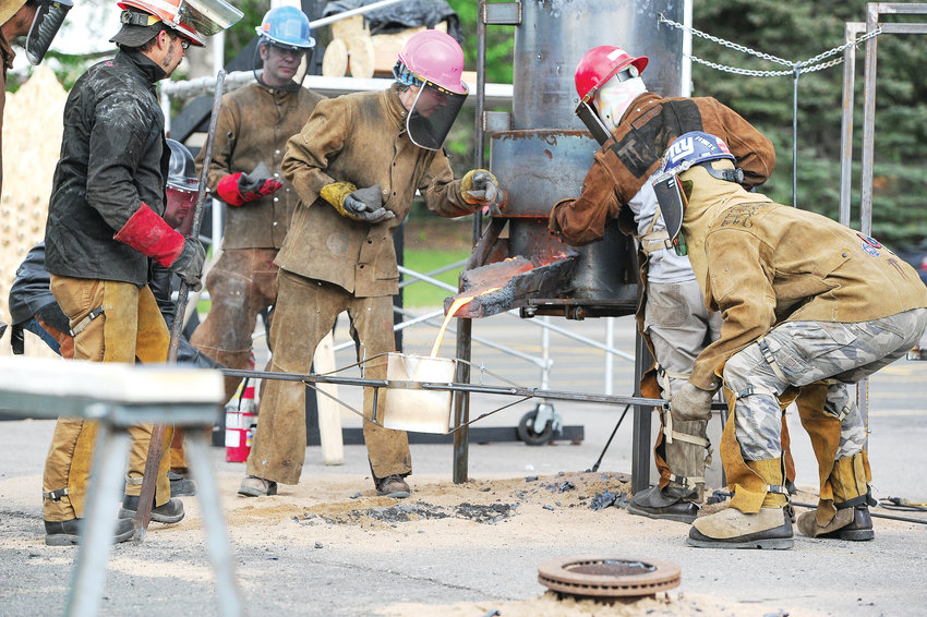 Metallurgist Ira Hill, left, of Birmingham, AL, supervises artists Sarah Harling of Denver (pink hat), and Jessie Blumenthal, of Missoula, MT, second from right, as they extract molten iron from a cupola furnace in the Northglenn City Hall parking lot, during a Community Iron Pour on June 5. Hosted by Northglenn Arts, the event was part of the city's 50th anniversary celebration.