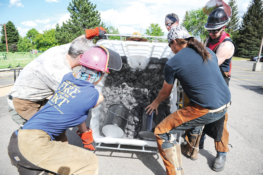 Artists and metallurgists ready a large bin of coke, a coal derivative, which will serve as fuel for a portable furnace, during Northglenn's Community Iron Pour June 5, outside Northglenn City Hall.