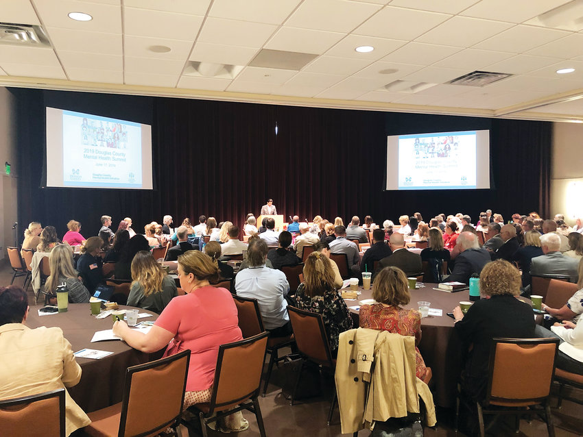 Commissioner Abe Layton speaks to a packed room at the 2019 Douglas County Mental Health Summit where professionals from various sectors of the mental health system met to discuss how care could be provided for local residents.