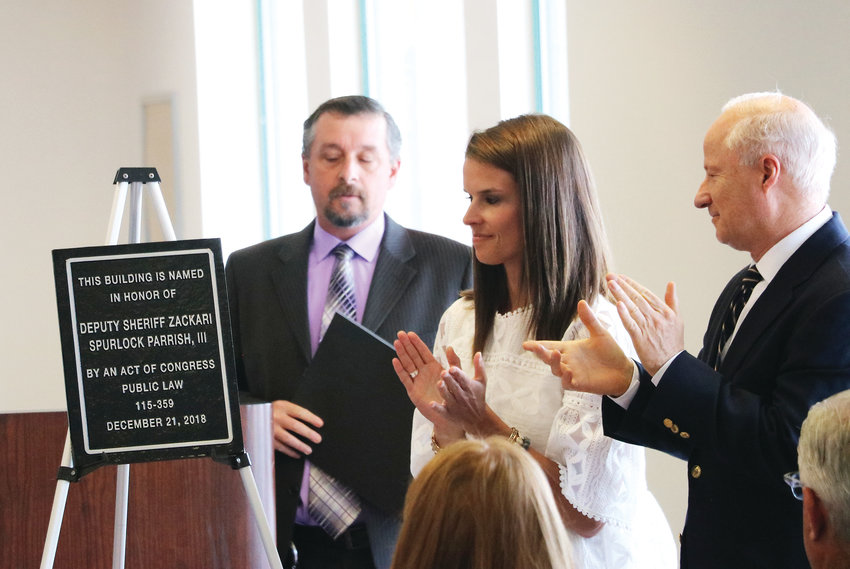 "Gracie Parrish, the wife of slain Douglas County Deputy Zackari Parrish, standing alongside former Congressman Mike Coffman and USPS Colorado/Wyoming District Manager Kevin Romero, applauds a plaque that now hangs on the east entrance of the Highlands Ranch Post Office. On June 17, the building was renamed the ""Deputy Sheriff Zackari Spurlock Parrish, III, Post Office Building."""