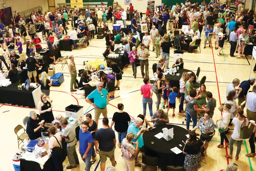 Eventgoers inside the Apex Center travel from booth to booth during Taste of Arvada 2019.
