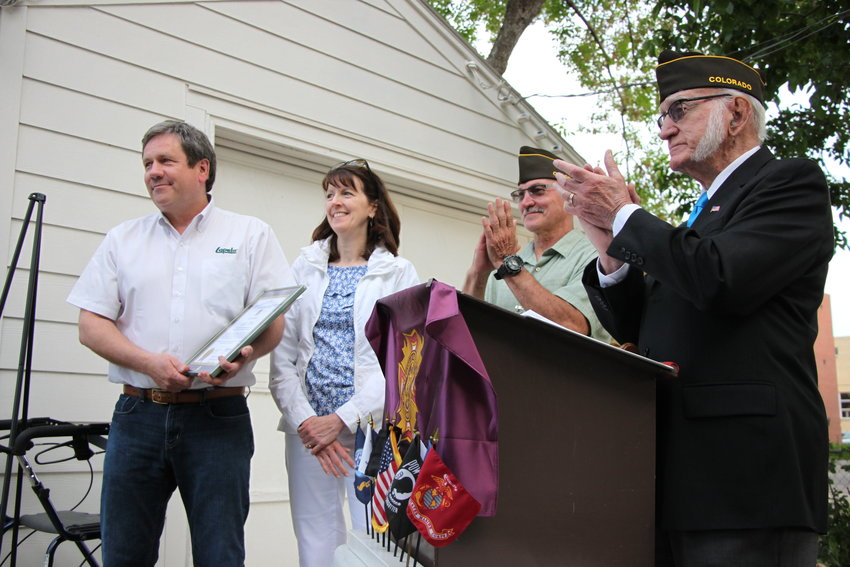 Veterans of Foreign Wars members Bill Baldaccini, right, and Lynn Kilian applaud Lapels Dry Cleaning owner Dave Wood and his wife Karen. Littleton's Pat Hannon VFW Post #4666 honored Wood for his practice of cleaning American flags and veterans' uniforms for free.