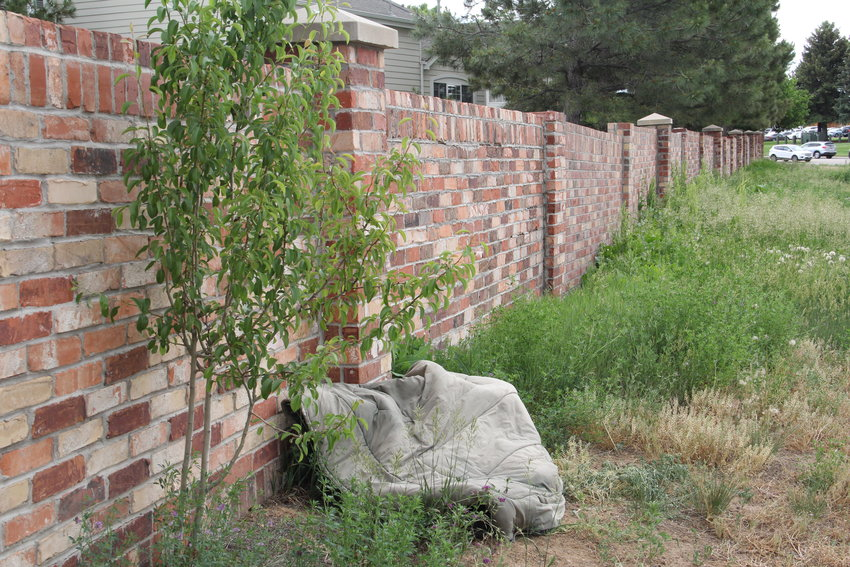 What appears to be a comforter or other bedding lies against a brick wall at the back side of a neighborhood near East Dry Creek Road and South Colorado Boulevard on June 21 in Centennial. City council is considering a ban on camping in certain areas after camping activity was reported in multiple parts of town.
