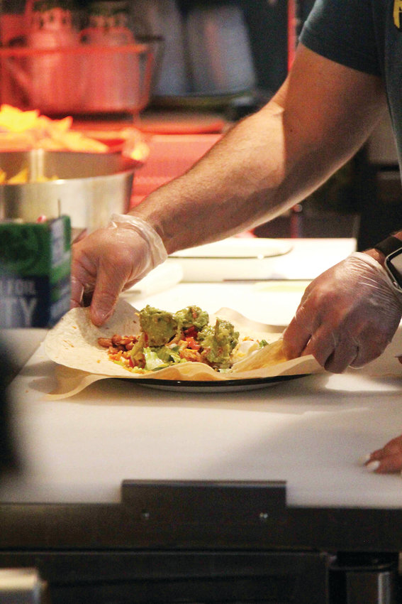 Jorge Romo makes a burrito at Romo's Street Tacos in Ecclesia food hall.
