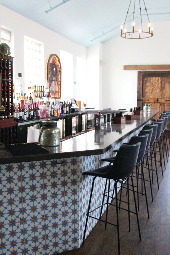 The bar upstairs in Ecclesia features a stainglass window from a historic home in Castle Rock.