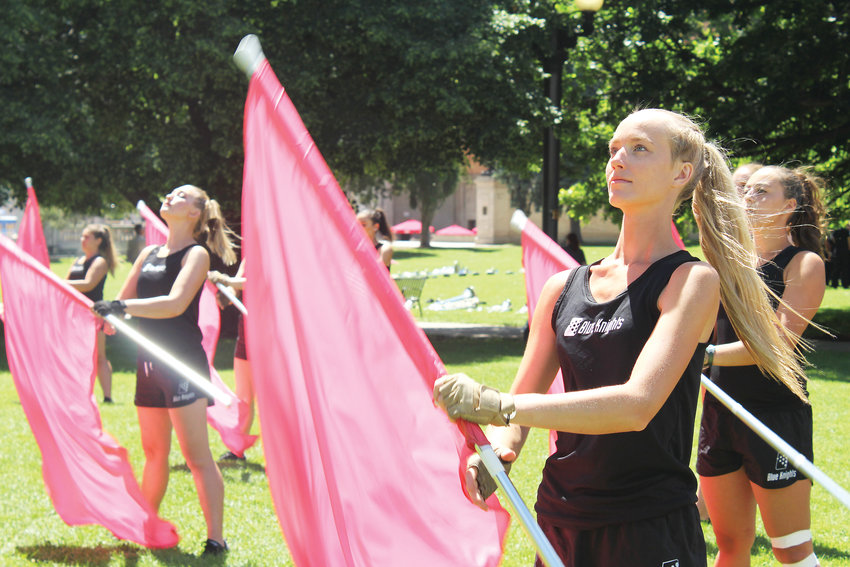 Katelyn Fabian with the Blue Knights Drum and Bugle Corps Color Guard practices before a performance at Civic Center park on June 20.