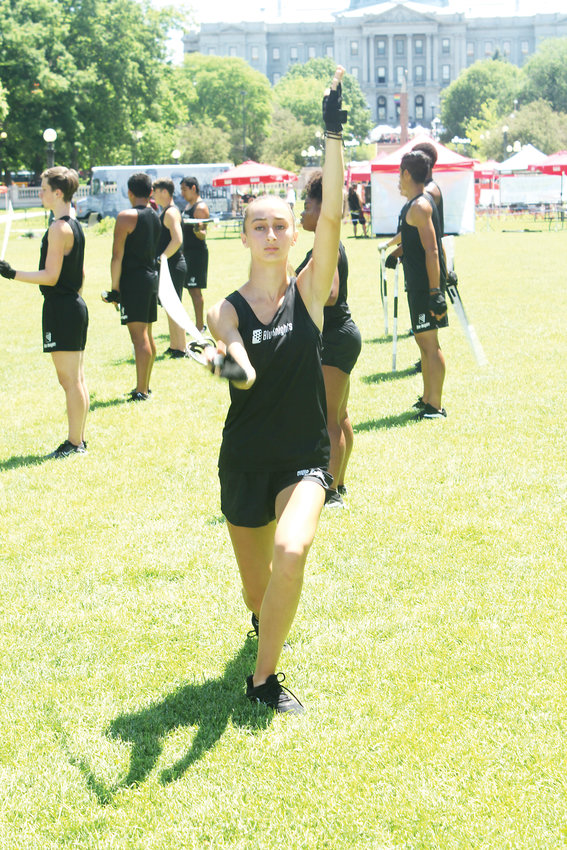 Claire Wells stretches before a Blue Knights performance in Denver. The drum corps performed during the Civic Center Eats event.