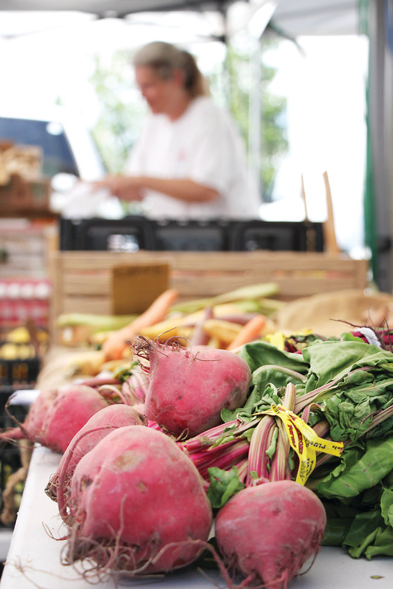 Dorreen Strnad of OLN Markets sells produce at the Aspen Grove Farmers Market on June 19. Beets have been one of few good crops that have come in so far this year, said OLN manager Jeremy Becker.