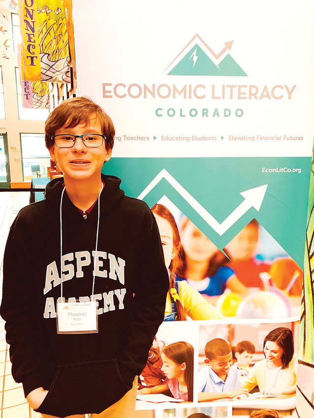 Thomas Pelz, a seventh-grader from Centennial, took first place in his age group in a statewide competition called the Stock Market Experience. Here, he stands next to a banner for Economic Literacy Colorado, a nonprofit that educates about financial literacy and puts on the competition.