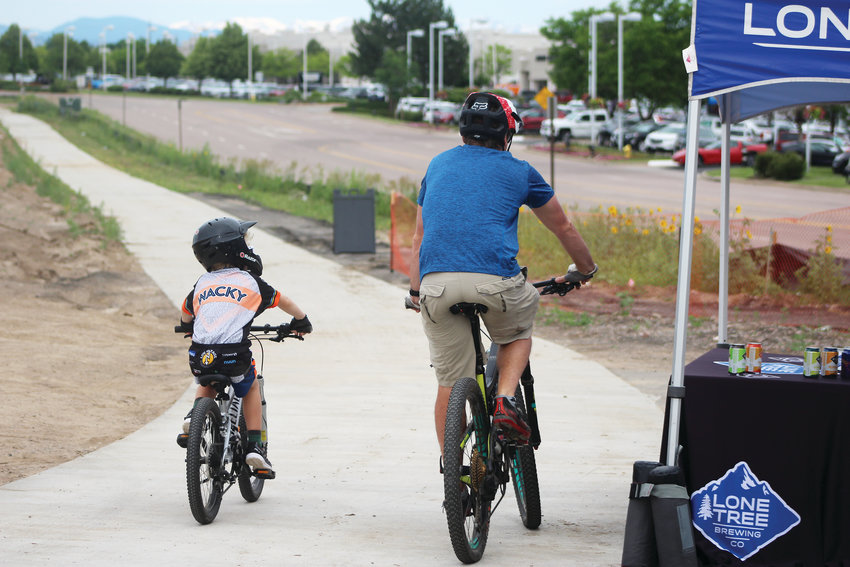 Tucker Wiseman and his father, Todd, head off on the Willow Creek Trail after stopping at the Lone Tree Bike to Work Day station. Tucker and his brother, Andrew, didn't have work on this day, June 26, but took the bikes out for a morning breakfast before a summer tutoring session.