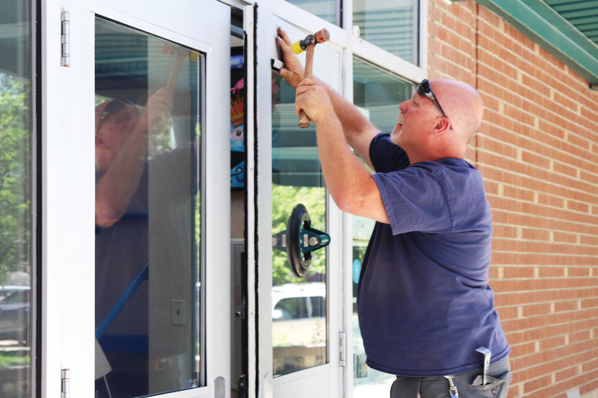 District glazier John Miller installs Laminated Security Glass, known for being difficult to break through, in the front doors at Arvada's Lawrence Elementary School.