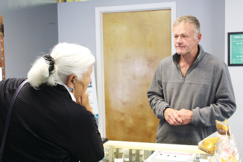 Todd Muck helps a customer at his business, Cannabis Bioscience Development in Franktown.
