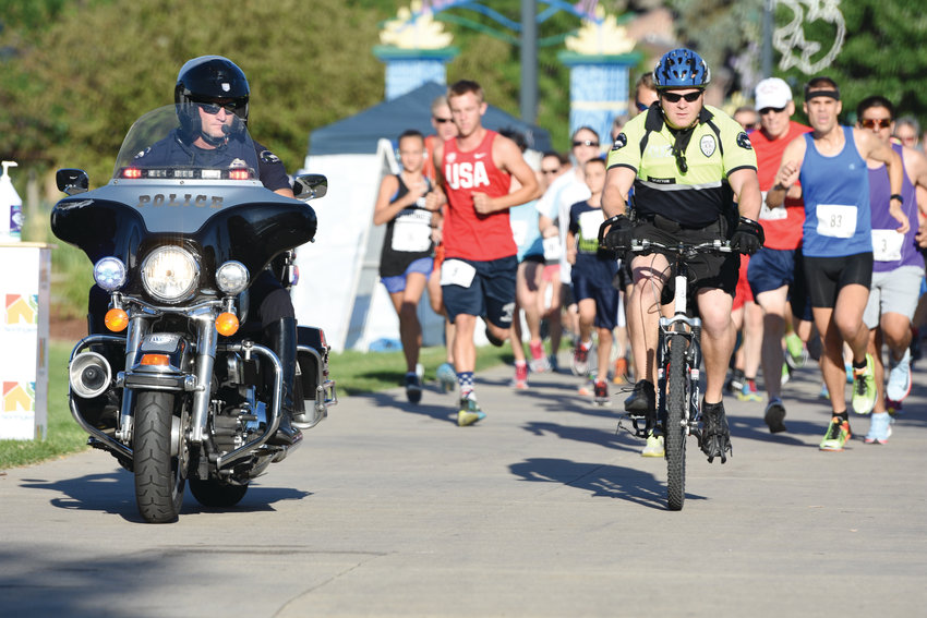 Northglenn Police escort runners at the start of the Firecrackers and Flapjacks Four Mile Run on July 4th at E. B. Rains, Jr. Park in Northglenn. The annual run was part of multiple activities conducted by the city on Independence Day.