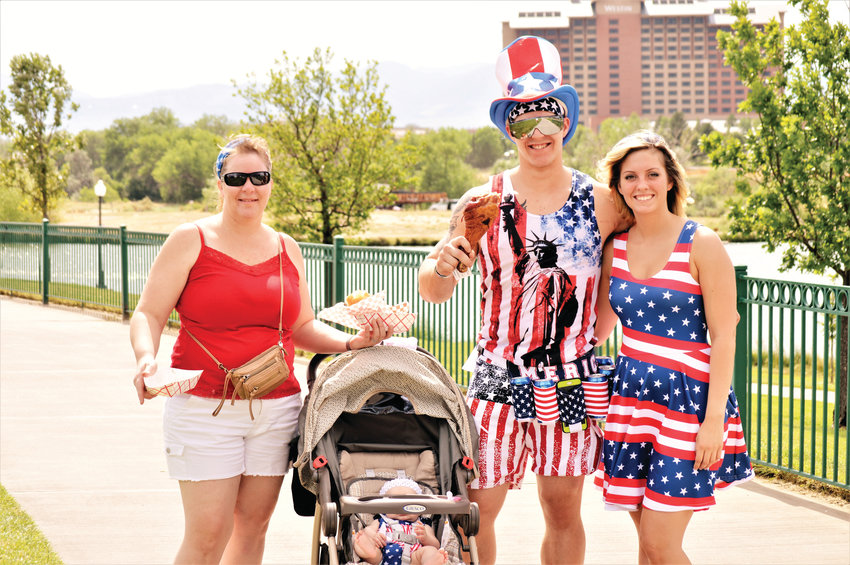 Left to right, Meg Haderlie, 43, Thomas Haderlie, 22, Shannon Rodriguez, 23 with four-month-old Serenity Haderlie in the baby carriage, are decked out in red, white and blue holiday finery as they make their way from the food trucks July 4 at Westminster's City Park.