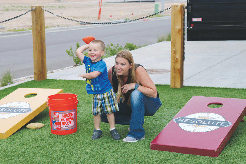 Jennifer Whittington and her son, Hunter, play cornhole on the lawn outside the taproom.