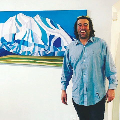 Genesee artist Topher Straus stands with one of his paintings. Straus' National Parks series will be exhibited at the American Mountaineering Museum in Golden from July 18 to Sept. 30. The public is invited to a free opening reception from 6-9 p.m.  July 18.