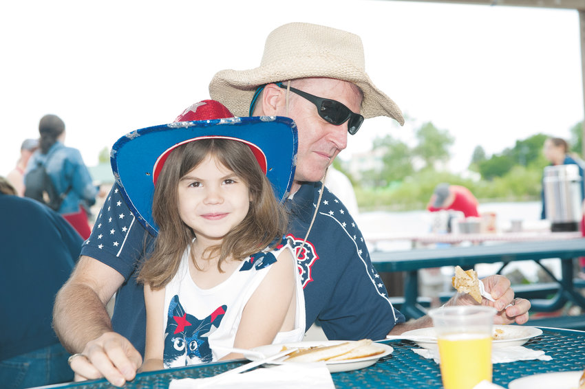 Jazmyn Wolcott, 6, and her father Jeff, of Thornton, enjoy a pancake breakfast during Boy Scout Troop 98's annual 4th of July Pancake Breakfast, at E.B. Rains, Jr. Memorial Park. The Wolcotts recently moved to Thornton from Wilburnham, MA.